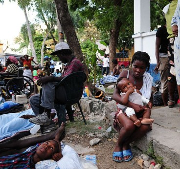 US_Navy_100116-N-2953W-385_A_Haitian_mother_comforts_her_child_at_the_Killick_Haitian_Coast_Guard_Base_clinic_as_a_member_of_the_U.N._security_team_stands_watch
